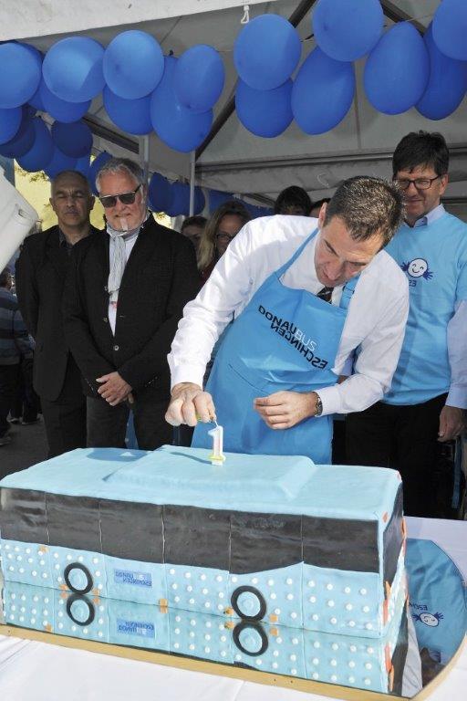 Oberbürgermeister Erik Pauly zündet die Geburtstagskerze auf der Donaubus-Torte an